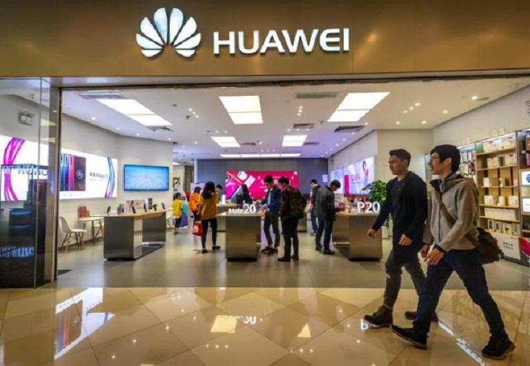 Personas caminan frente a la tienda de Huawei en Guangzhou, China. (EFE)