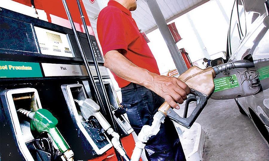 Empleado de estación despacha combustibles.