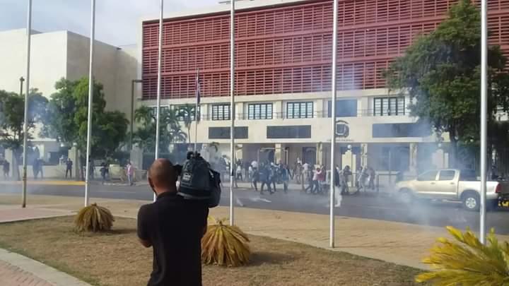 Agentes policiales lanzan bombas lacrimógenas a manifestantes.