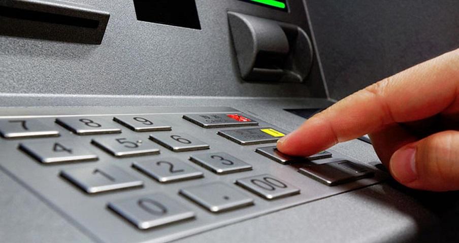Hombre manipula un cajero automático al realizar una transacción.
