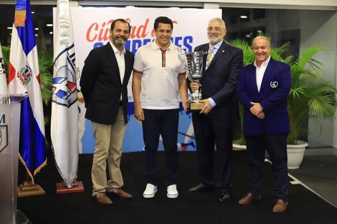 David Collado, alcalde y Vitelio Mejía, presidente de LIDOM sostienen la copa que estará en juego en el City Champ. Figuran José Miguel Bonetti y Miguel Angel Fernández.