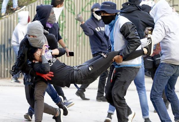 Estudiantes traslandan a joven herido durante las manifestaciones del 26 de noviembre.( Foto AP)