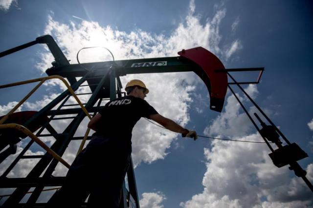 Un trabajador comprueba un cable de una estación de bombeo de petróleo. EFE/Martin Divisek/Archivo