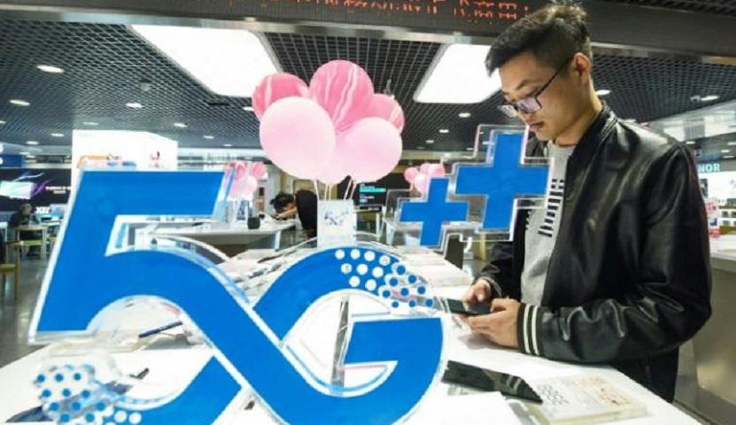 Un cliente mira un teléfono móvil junto a un logotipo de tecnología 5G en una tienda en Hangzhou, China.