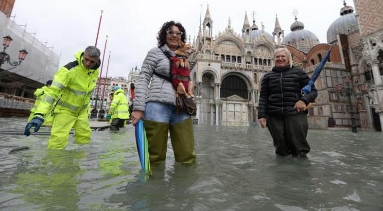 Personas en Venecia con el agua al cuello.(Foto EFE/EPA/Andrea Merola)
