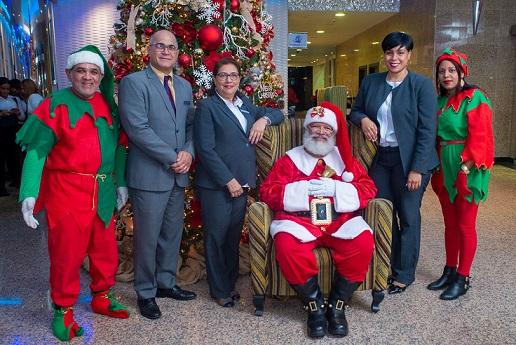 Genaro Santos, Rosario Sangiovanni (Charo) y Katiuska Méndez, con Santa Claus y su duendes.(Foto externa)