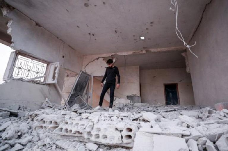 Joven sirio camina sobre los escombros de un edificio destrozado por supuestos ataques aéreos.