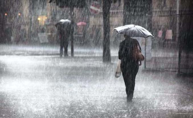 Mujer caminando bajo la lluvia en RD.(Foto externa)