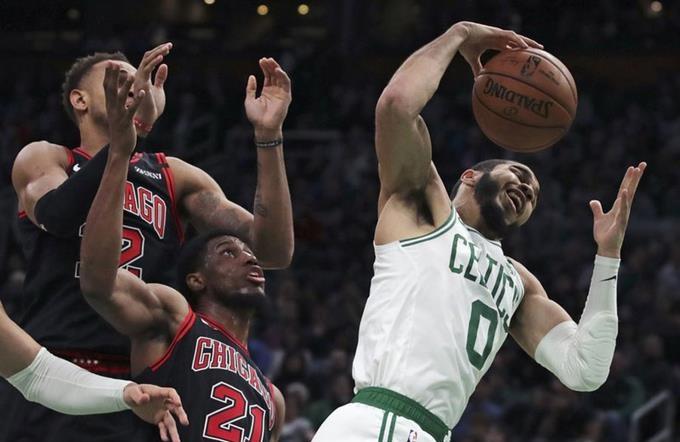 Jayson Tatum, alero de los Celtics de Boston, atrapa un rebote frente a Thaddeus Young, de los Bulls de Chicago.(Foto: AP)