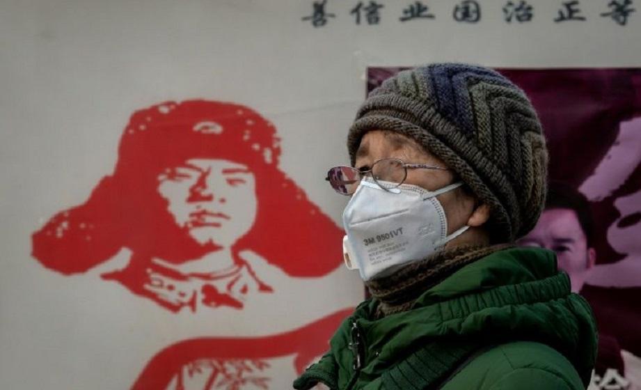Una mujer con mascarilla de protección contra la epidemia de coronavirus, cerca de la estación de trenes de Pekín.