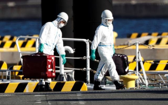 Oficiales con equipo de protección llevan maletas después que las personas que fueron transferidas desde el crucero Diamond Princess llegaran a la base de la policía marítima en Yokohama, al Sur de Tokio, Japón.(Foto: externa)