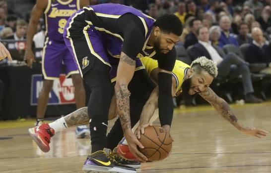 El jugador de los Warriors de Golden State Ky Bowman toca un balón de Anthony Davis, de los Lakers de Los Ángeles, en la primera mitad del juego de la NBA que enfrentó a ambos equipos, en San Francisco, el 27 de febrero de 2020. (Foto: AP/JEFF CHIU)