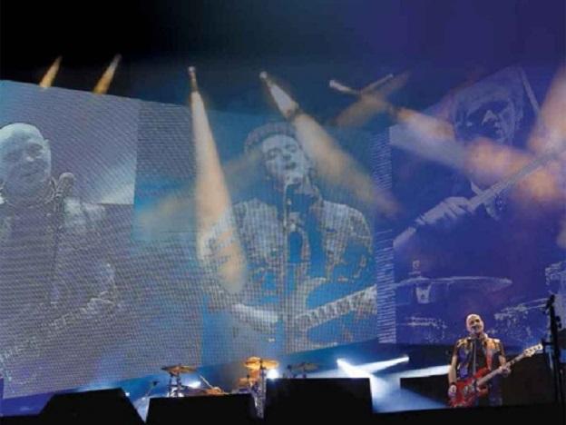 """Con el difunto cantante Gustavo Cerati en pantalla, Charly Alberti de Soda Stereo toca durante el primer concierto de su gira """"Gracias totales""""."""