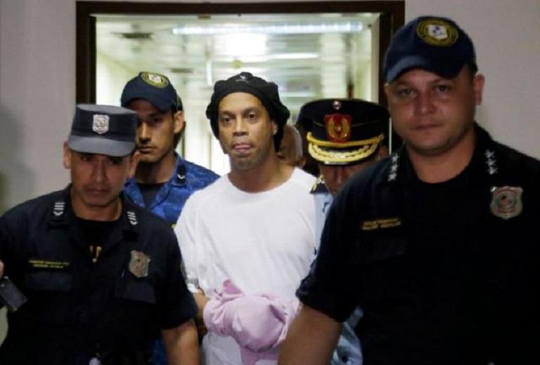 El exfutbolista brasileño Ronaldinho avanza esposado en la Corte Suprema de Paraguay, en Asunción.