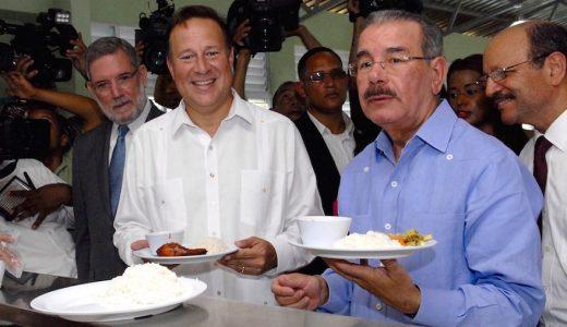 Los presidentes Danilo Medina y Juan Carlos Varela reciben su ración alimenticia en la escuela Padre Eulalio Antonio Arias. (Fuente: externa)