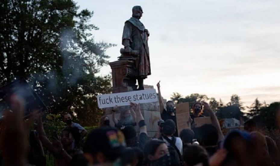 Manifestantes rodeando la estatua de Cristóbal Colón poco antes de derribarla en Richmond, Virginia. (foto PARKER MICHELS-BOYCE/AFP via Getty Images)