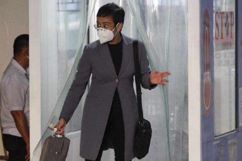 Maria Ressa, con mascarilla, sale de una zona de desinfección antes de asistir a una vista judicial en Manila, en Filipinas. (Fuente: AP/Aaron Favila)
