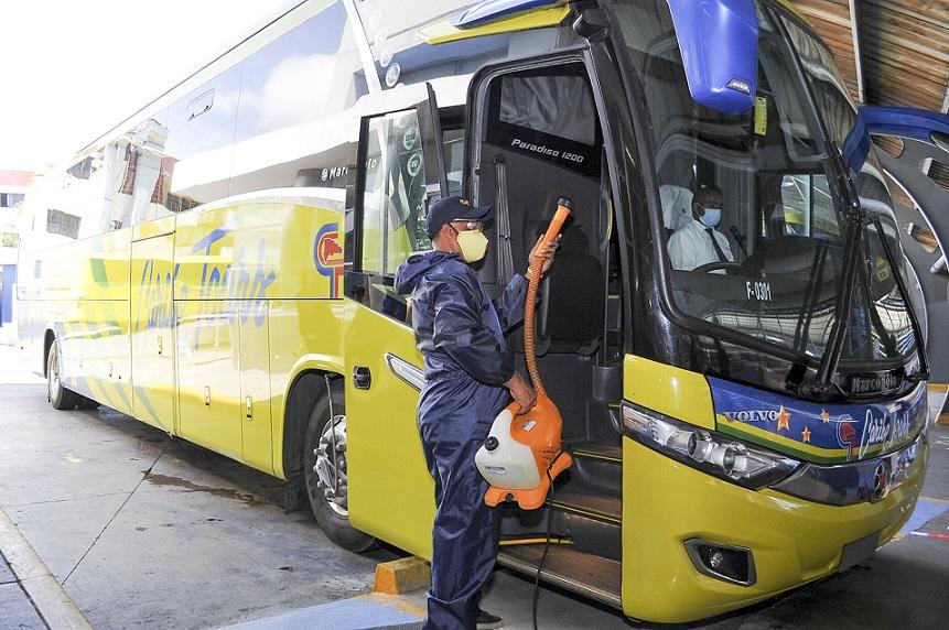 Uno de los autobuses de Caribe Tours es sometido a la desinfección.