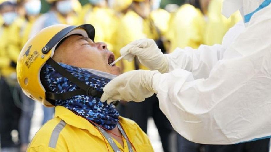Un trabajador sanitario en un traje protector realiza una prueba de ácido nucleído para un repartidor, en Pekín, China.