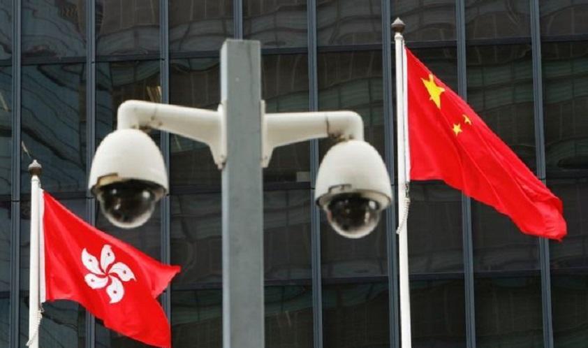 Las banderas nacionales de Hong Kong y China ondean detrás de un par de cámaras.