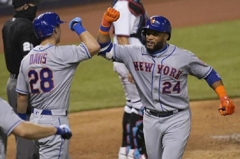 Robinson Canó (24), de los Mets de Nueva York, choca los codos con JD Davis.