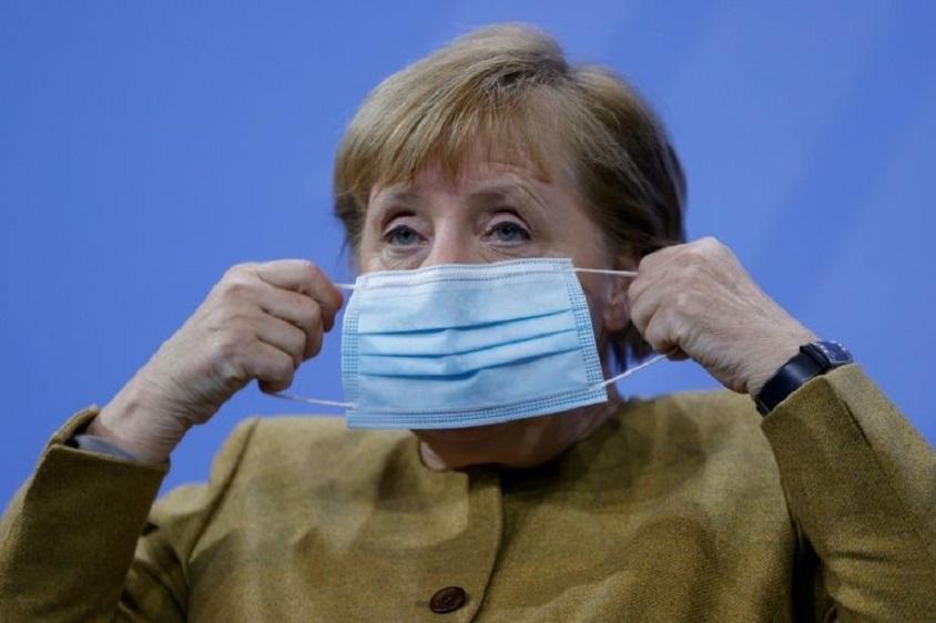 La canciller alemana Angela Merkel se pone una mascarilla. (Fuente: EFE)