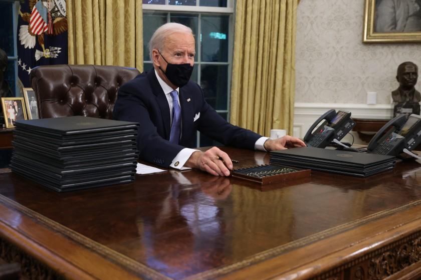 Biden firma leyes en su escritorio de la Casa Blanca.