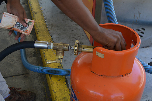 Llenan cilindro en estación de gas.