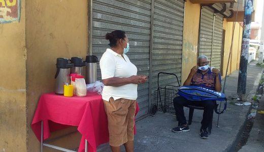 Doña Celeste atiende cliente en su puesto de venta.