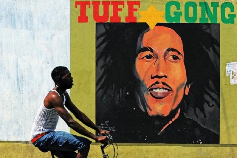 Un hombre en bicicleta pasa frente a un mural de Bob Marley en Kingston, Jamaica.
